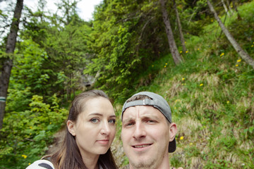 Backlit portrait of couple taking selfie photo in a forest