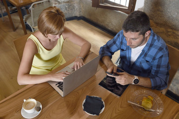 couple using laptop computer and mobile phone networking ignoring each other