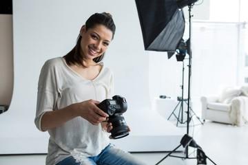 Portrait of female photographer holding digital camera