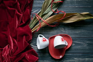 Rustic set of red andvelor two white coffee cups with printed hearts on heart shaped plate and leaves on grey background. Space for text