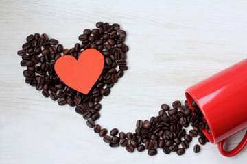 love potion/ a lot of coffee beans in form of heart, redischarge from a red cup on the table