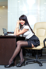 Young sexy woman in black stockings sitting on workplace in  off