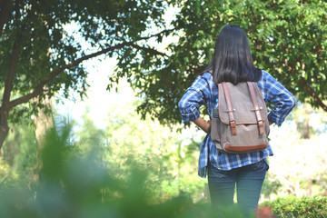 Happy Asian girl backpack in park and forest background, Relax time