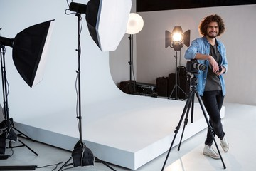 Happy male photographer standing in studio