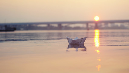 paper boat on the water during beautiful sunset with reflection sun in sea