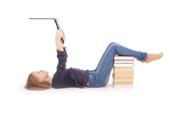 Student teenage girl lying sideways on the floor with laptop