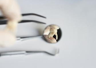 Pull the aching tooth reflected in the dental instruments