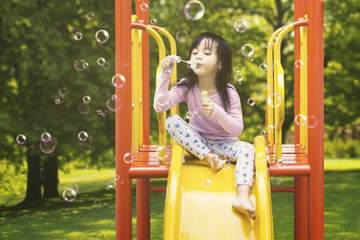 Girl blowing soap bubbles on slide
