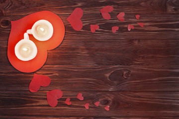 Red hearts and  candle on a wooden board.