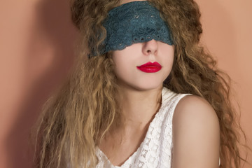 Portrait of attractive woman blindfolded with lace ribbon
