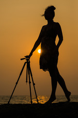 woman photographer in the sunset on the ocean