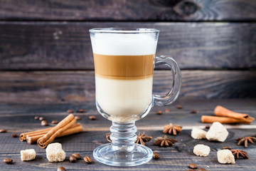 Hot latte macchiato coffee with tasty foam in tall clear glass on dark wooden table serving with cinnamon, cane sugar and roasted coffee beans.
