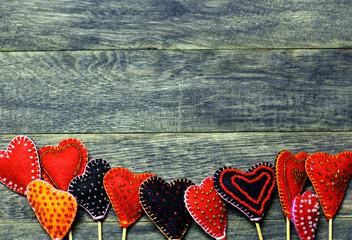 Bottom frame border of Handmade felt colorful hearts on dark old wooden background. Love card for Valentine's day. Concept with big copyspase for hand crafts or DIY illustration.