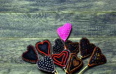 Handmade felt hearts on dark old wooden background. One heart different colors. Love card for Valentine's day. Concept with big copyspase for hand crafts or DIY illustration.