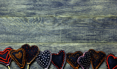Bottom frame border of Handmade felt hearts on dark old wooden background. Love card for Valentine's day. Concept with big copyspase for hand crafts or DIY illustration.