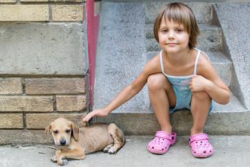 little girl cuddle a puppy