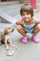 little girl feeding a puppy
