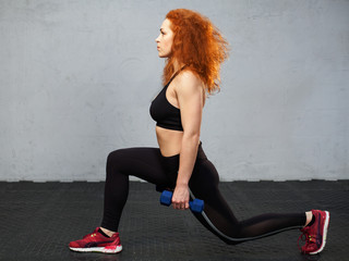 Young ginger woman performing frontal lunge with the dumbbells at the gym