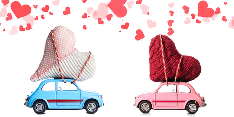 Couple of retro toy cars delivering craft hearts for Valentine's day on white background with flying cars
