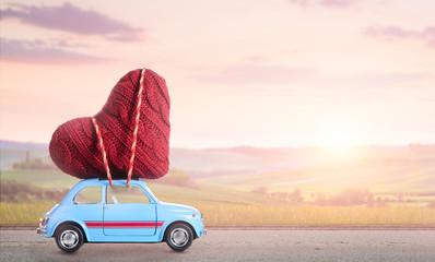 Blue retro toy car delivering heart for Valentine's day against blurred sunset rural landscape