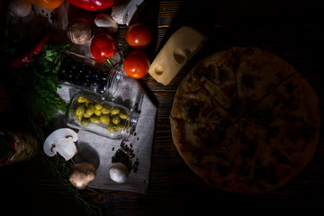 High angle view of pizza with olives, near lie cheese and other vegetables on napkin on wooden table