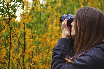 Girl photographing blossoming tree