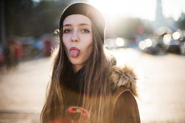 Cheerful positive girl showing tongue looking at camera