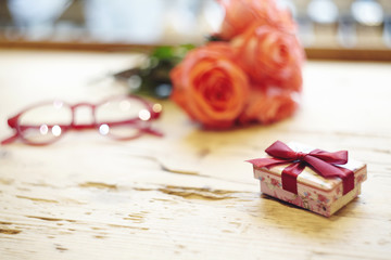 Small present box with bow on wooden table. Focus on bow. Red roses flowers behind on wooden table. St. Valentine's day concept. Blank space for text