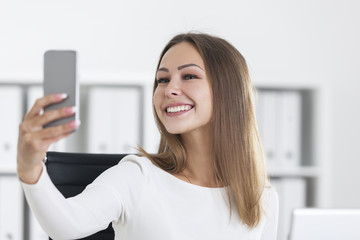 Close up of smiling woman in office making selfie