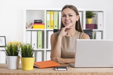 Portrait of a smiling girl in beige in office