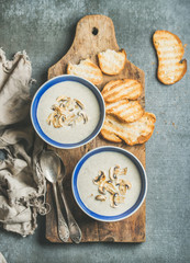 Creamy mushroom soup in bowls with toasted bread slices on rustic serving board over grey concrete background, top view