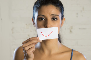 young beautiful depressed woman hiding her sorrow and sadness behind a paper with a drawn smile