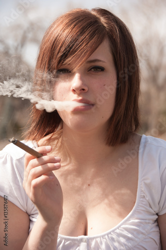 cute brunette exhales smoke out of her mouth. outside smoking a