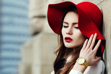 Young beautiful fashionable woman posing on street. Model looking down, wearing stylish hat, wrist watch. Female fashion concept. Outdoor close up portrait. City lifestyle. Copy, empty space for text