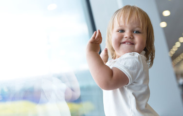 smiling baby girl near window