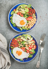 Healthy breakfast with fried egg, chickpea sprouts, seeds, fresh vegetables and greens in blue bowls over grey concrete background, top view. Clean eating, healthy lifestyle, vegetarian food concept