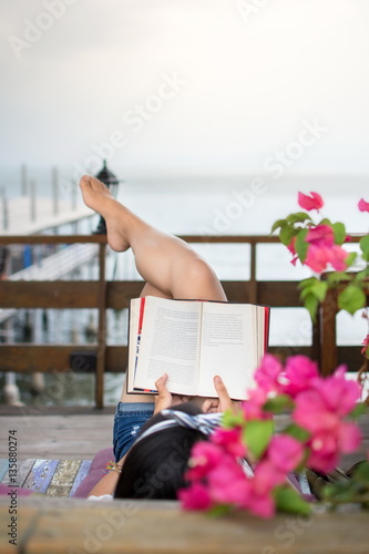 Girl reading book on the balcony with seaside view for The balcony book