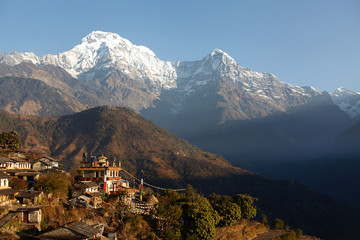 Amazing landscape of gorgeous gigantic mountains and cliffs of the Himalayas standing high above village down in valley. Small Nepali settlement surrounded with green slopes and grand snowy peaks