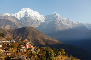 Scenic view of houses of small Nepali village surrounded with green slopes and gigantic cliffs of the picturesque Himalayan mountains in background with white snow capped peaks. Travel and adventure