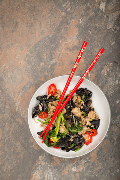 Wood ear mushroom stir-fry with ground meat and red peppers. Brown stone background. Red chopsticks on top of the plate