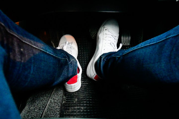 close up man foot step on the car accelerator, wearing white shoe and blue jean