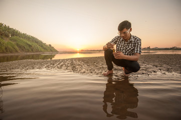 Scientist or biologist working on water analysis near the river.