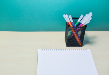 Group of colorful pen and note book on wood table.