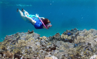 Woman snorkeling underwater over a coral reef in Fiji