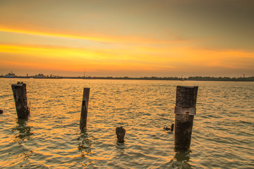 Wooden pier or jetty remains on blue lake sunset and sky reflection water, Thailand.