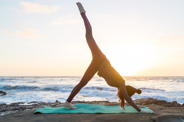 Girl in red bottoms, gray jacket and black hat doing yoga on a green yoga mat near the ocean at sunset. Leg up