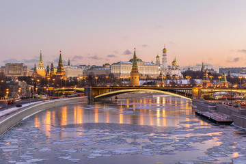 Illuminated Moscow Kremlin and Moscow river with ice lumps in winter morning. Clear pink colorful sky.