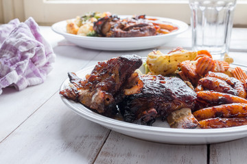 Slow cooked ribs with homemade pasta and grilled vegetables served on a wooden table