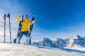Mountaineer backcountry ski resting along a snowy ridge with ski