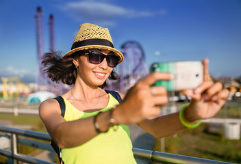 Woman using smartphone to take selfie photo in amusement park at roller coaster background